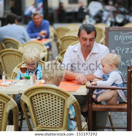 Family, a father with three children, two teenager twins sons, and little cute baby girl, having fun in cafe on summer terrace in a center of busy city street, boys playing with gadget smart phone  - stock photo