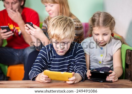 Family activities for the games on smartphones, all sitting with gadgets - stock photo