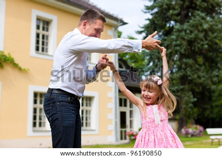 Family affairs - father and daughter playing in summer; he is dancing with her in the garden in front of the house - stock photo