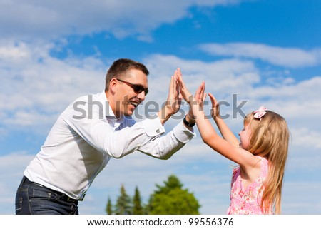 Family affairs - father and daughter playing in summer; he is dancing with her while having a walk - stock photo