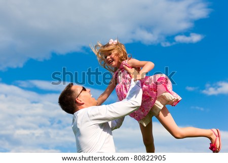 Family affairs - father and daughter playing in summer; he is throwing her into the air - stock photo
