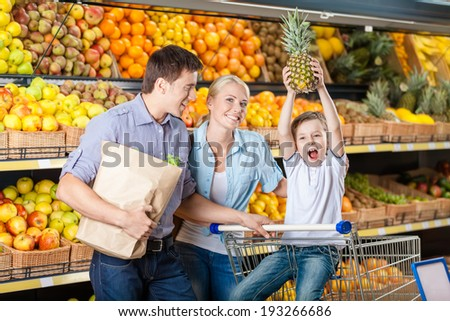 Family against shelves of fruits goes shopping. Father keeps a packet with fruits and vegetables, son hands pineapple