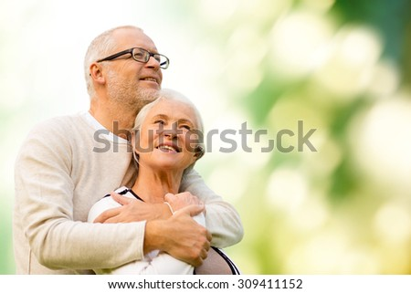 family, age, love, relations and people concept - happy senior couple over green natural background - stock photo