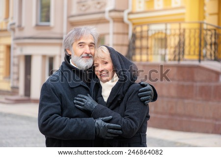 family, age, tourism, travel and people concept - happy senior caucasian couple hugging on city street - stock photo