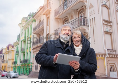 family, age, tourism, travel and people concept - senior couple with digital tablet and city guide on street - stock photo