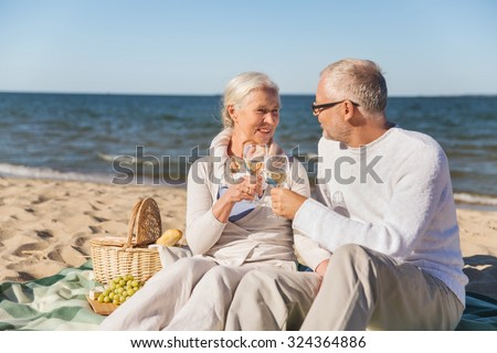 family, age, travel, tourism and people concept - happy senior couple having picnic and talking on summer beach - stock photo