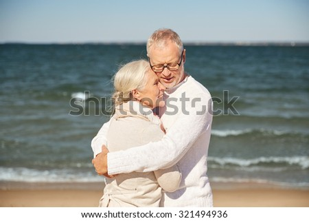 family, age, travel, tourism and people concept - happy senior couple hugging on summer beach - stock photo