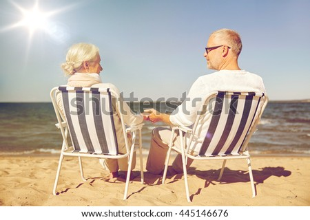 family, age, travel, tourism and people concept - happy senior couple resting in folding chairs on summer beach from back - stock photo