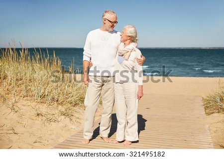 family, age, travel, tourism and people concept - happy senior couple talking on summer beach - stock photo