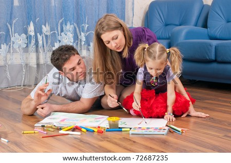 Family amicably draw on a floor - stock photo