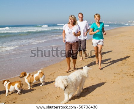 family and family dogs running on beach