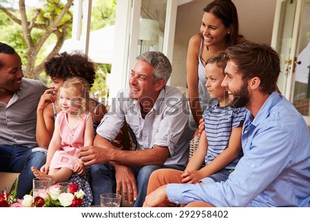 Family and friends gathered in a conservatory - stock photo