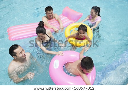 Family and friends playing in water at the pool with inflatable tubes - stock photo