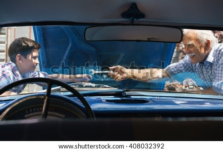 Family and Generation gap. Old grandpa spending time with his grandson. The senior man asks the preteen child to help him fixing the engine of a vintage car from the 60s. They smile happy.  - stock photo
