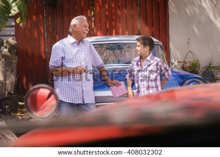 Family and Generation gap. Old grandpa spending time with his grandson. The senior man talks vintage car with the boy and lean against the hood of an automobile from the 60s - stock photo