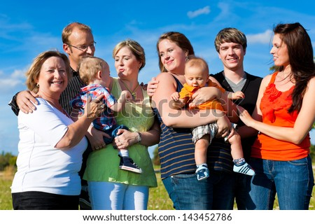 Family and multi-generation - mother, father, children and grandmother having fun on meadow in summer - stock photo