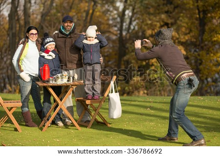 Family and picnic concepts. Young family spending free time on a picnic with friends. Man making photos of a whole family in the park. - stock photo