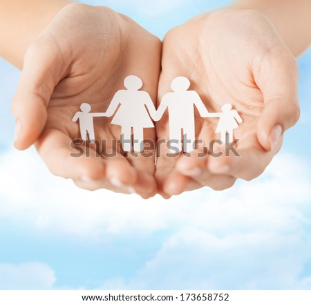 family and relations concept - closeup of female cupped hands showing paper man family