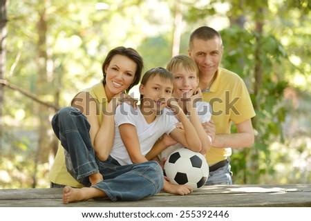 Family and socker ball in summer park - stock photo