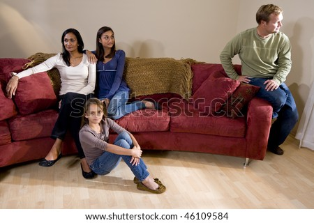 Family argument - girls on one side of sofa with father sitting apart - stock photo