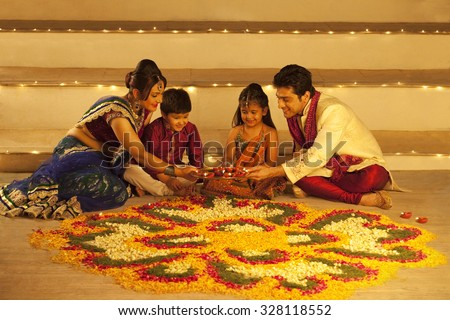 Family arranging diyas on rangoli - stock photo
