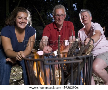 Family at campfire in the garden with marshmallows - stock photo