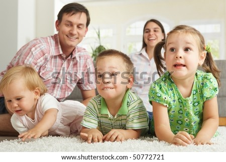 Family at home: happy children with their parents lying on floor making faces. - stock photo