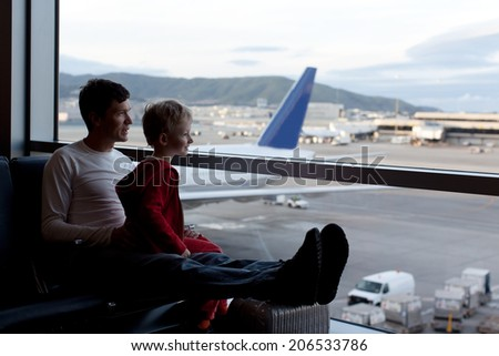 family at the airport waiting for departure - stock photo