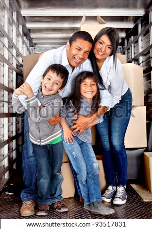 Family at the back of a moving truck ready to go to their new house - stock photo