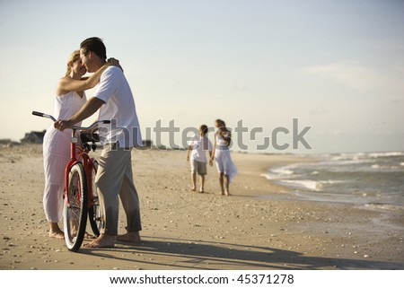 Family at the beach with the mother and father snuggling in the foreground. Horizontal shot. - stock photo