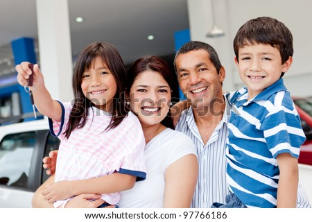 Family at the dealership buying a new car and holding keys - stock photo