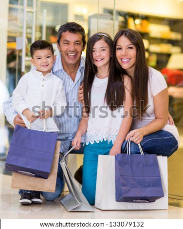 Family at the shopping center looking very happy - stock photo