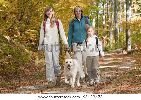 Family autumn trekking with dog - stock photo