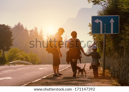 Family backpackers goes on mountain road at sunset - stock photo