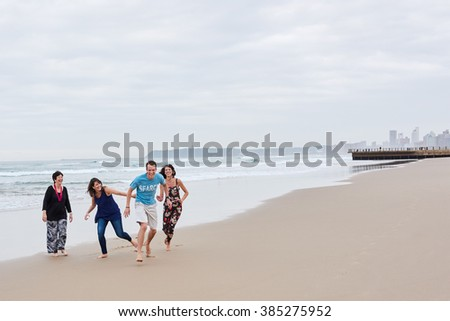 Family being playful together on the beach - stock photo