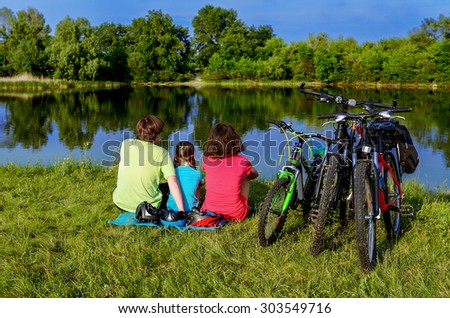 Family bike ride outdoors, active parents and kid cycling and relaxing near beautiful river  - stock photo