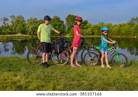Family bikes ride outdoors, active happy parents and kid cycling and relaxing near beautiful river