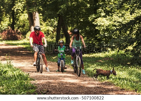 Family biking in forest with dog running next to them