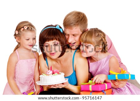 Family blowing out candle fire on birthday cake - stock photo