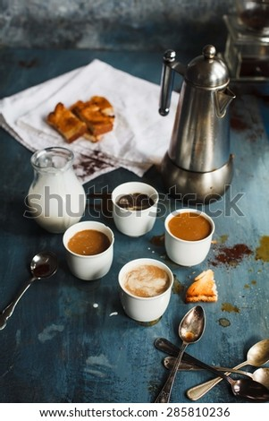Family Breakfast coffee concept. Cups of black coffee, espresso drink and cappuccino with jug of milk and metal coffeemaker served on blue rustic table with kitchen tools. - stock photo