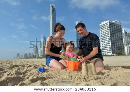 Family builds sand castle on Surfers Paradise main beach in Gold Coast Queensland, Australia. - stock photo