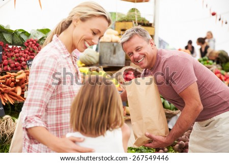 Family Buying Fresh Vegetables At Farmers Market Stall - stock photo