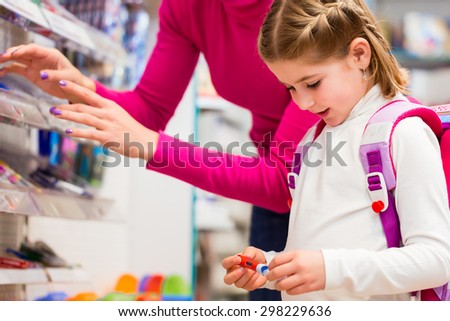 Family buying school supplies in stationery store, little girl looking at a fountain pen - stock photo