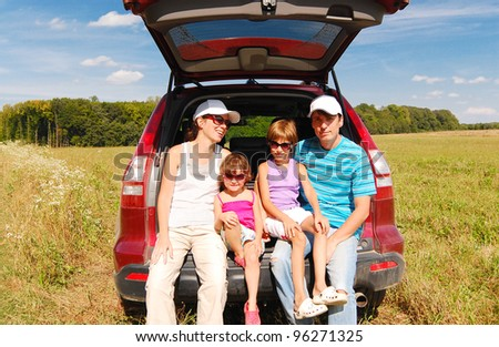 Family car trip on summer vacation. Happy active parents and two kids near car having fun outdoors