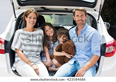 Family car trip on summer vacation. Happy smiling parents and two children in car having fun. Cute small boy holding teddy bear sitting with sister and parents in car for road trip with car.  - stock photo
