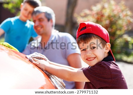 Family car wash, little boy cleaning spotlight, father and brother in background - stock photo