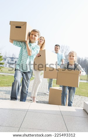 Family carrying cardboard boxes while entering new house - stock photo