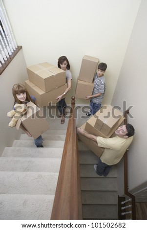 Family carrying moving boxes up stairs
