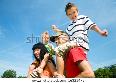 Family carrying their two kids piggyback under a perfect blue sky