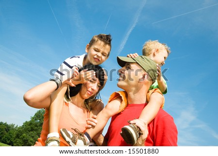 Family carrying their two sons on their shoulders under a perfect sky - stock photo